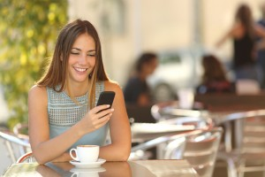 Woman sitting at cafe table smiling at cell phone